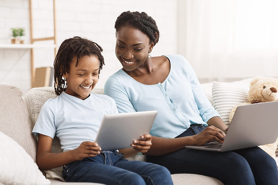 Blog - Mother and Daughter Doing Work on the Sofa at Home